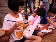 Interesados niños en elaborar máscaras para Festival del Medio Otoño